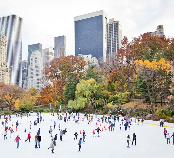 Beautiful fall view of people ice skating at Wollman Rink in Central Park